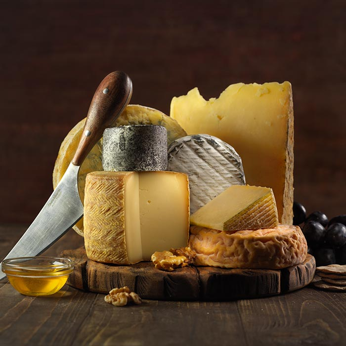 Photo of cheeses on rustic wooden boards
