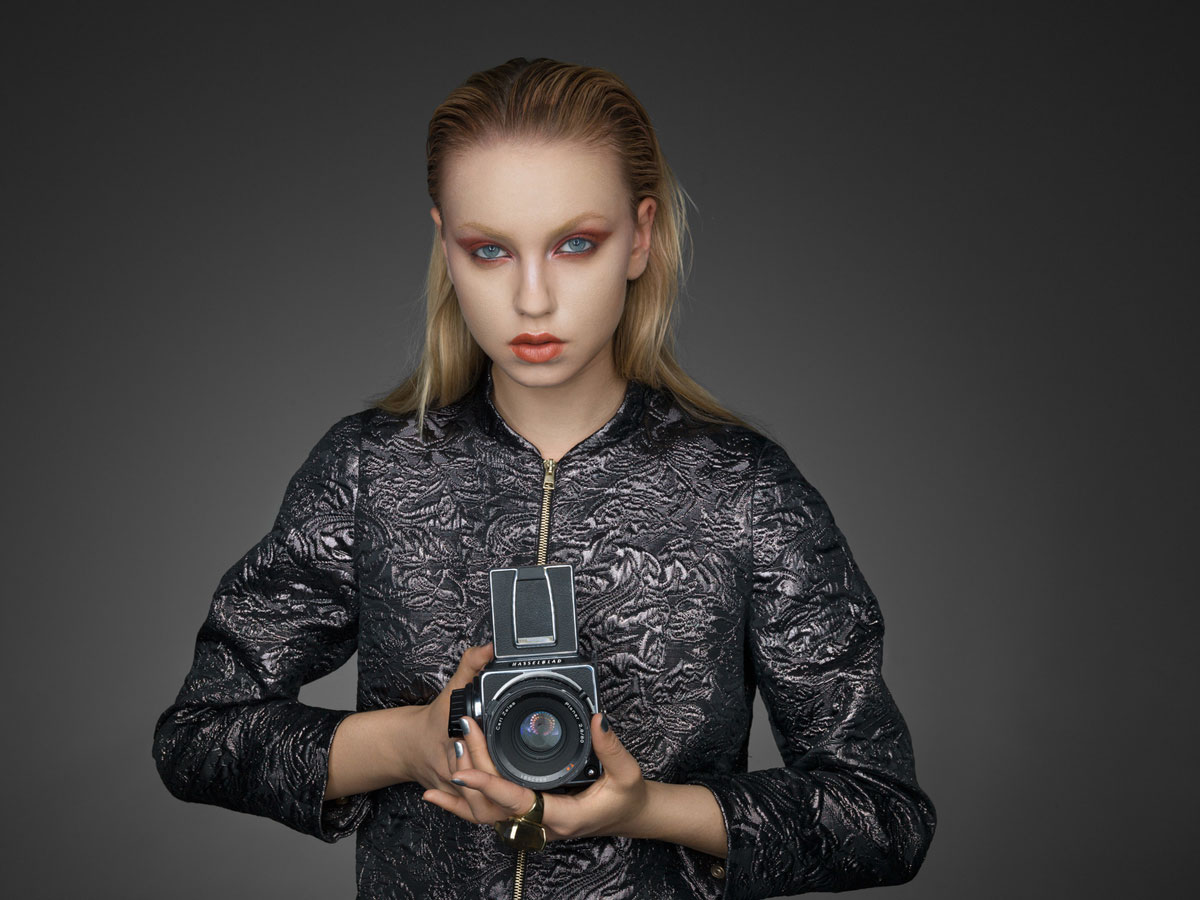 Model holding professional camera. Portrait by Karl Taylor