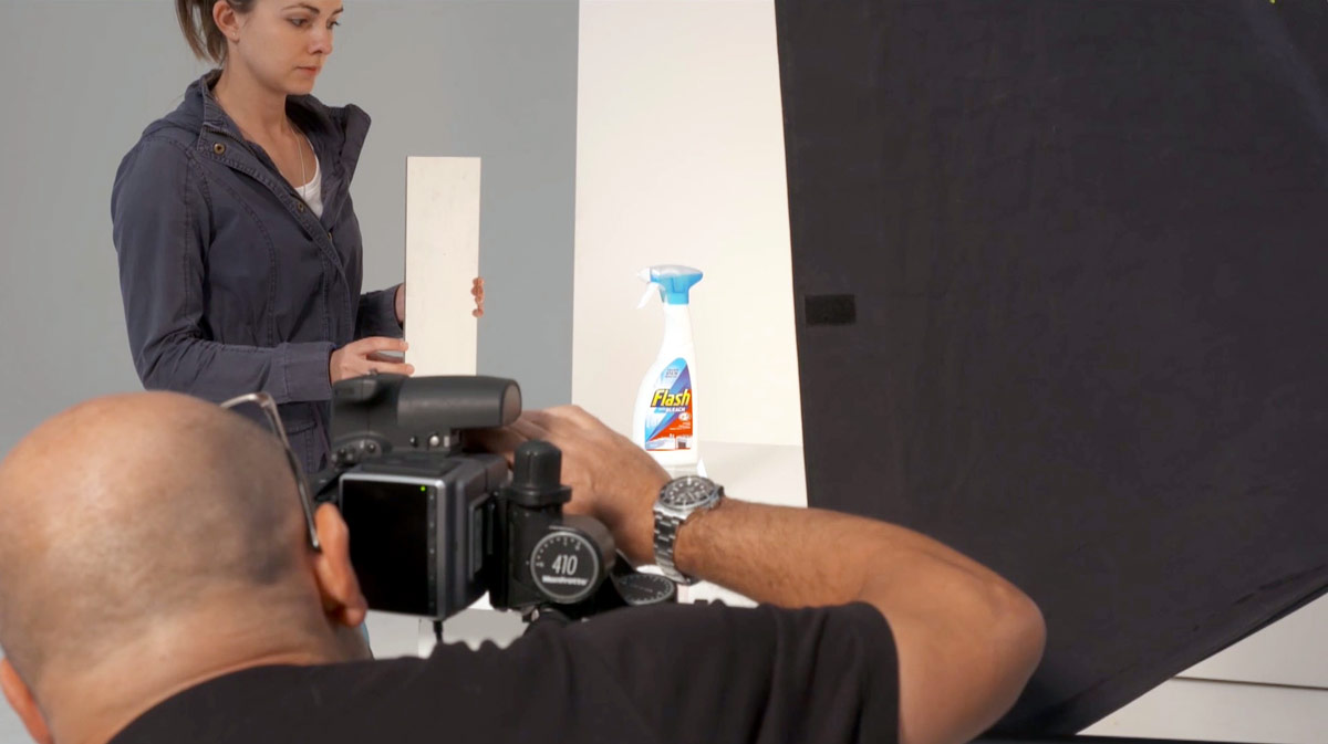Ashleigh helping Karl during a pack shot setup showing lighting and reflector card