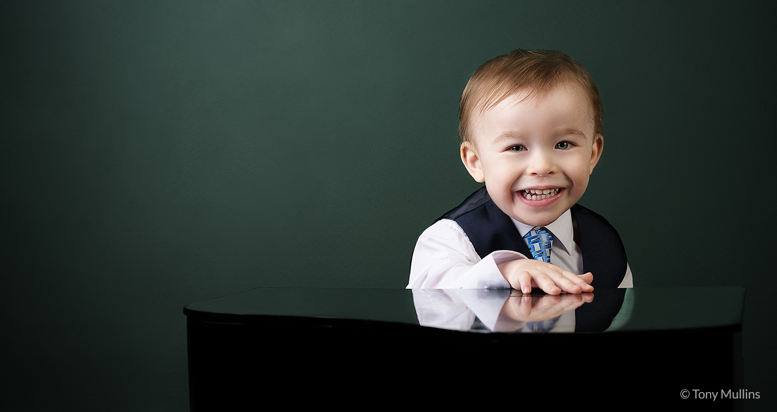 A playful portrait of a child next to a mini piano.